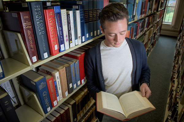 Student opening a book in Southern campus library