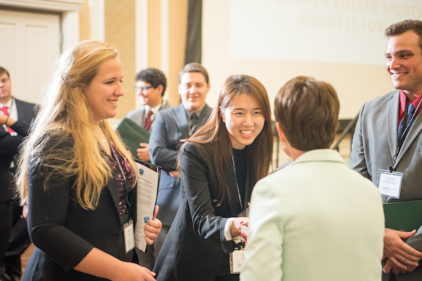 Attendees shake hands at a career fair