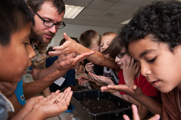 Children gather around bugs for inspection with the teacher
