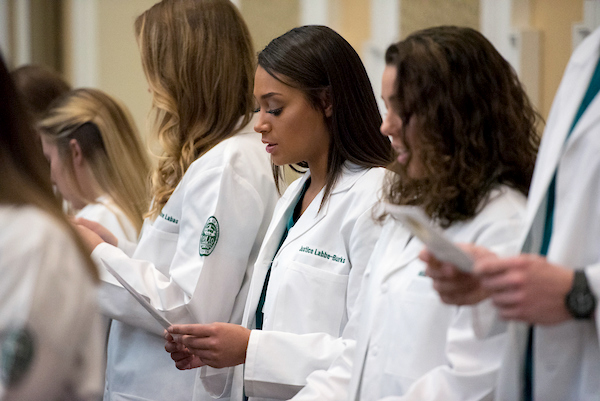 Doctors line up at a white coat ceremony